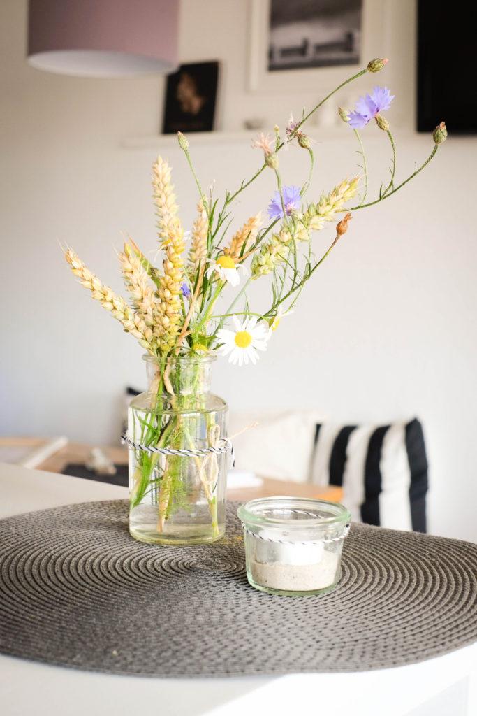 Dieses Bild zeigt, wie liebevoll im Qunitings nicht nur die Burger zubereitet, sondern auch die Tische dekoriert werden.