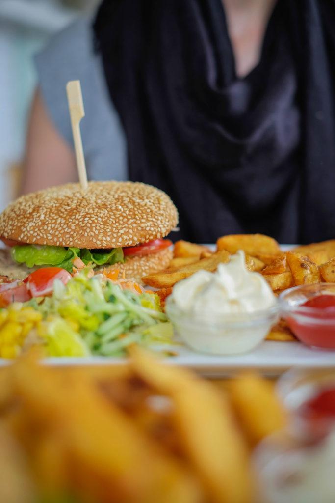 Dieses Bild zeigt die frisch zubereiteten Kartoffelecken und den BioFleisch- Burger aus regionaler Zucht. Selbst das Brötchen wird eigens für das Quintings produziert.
