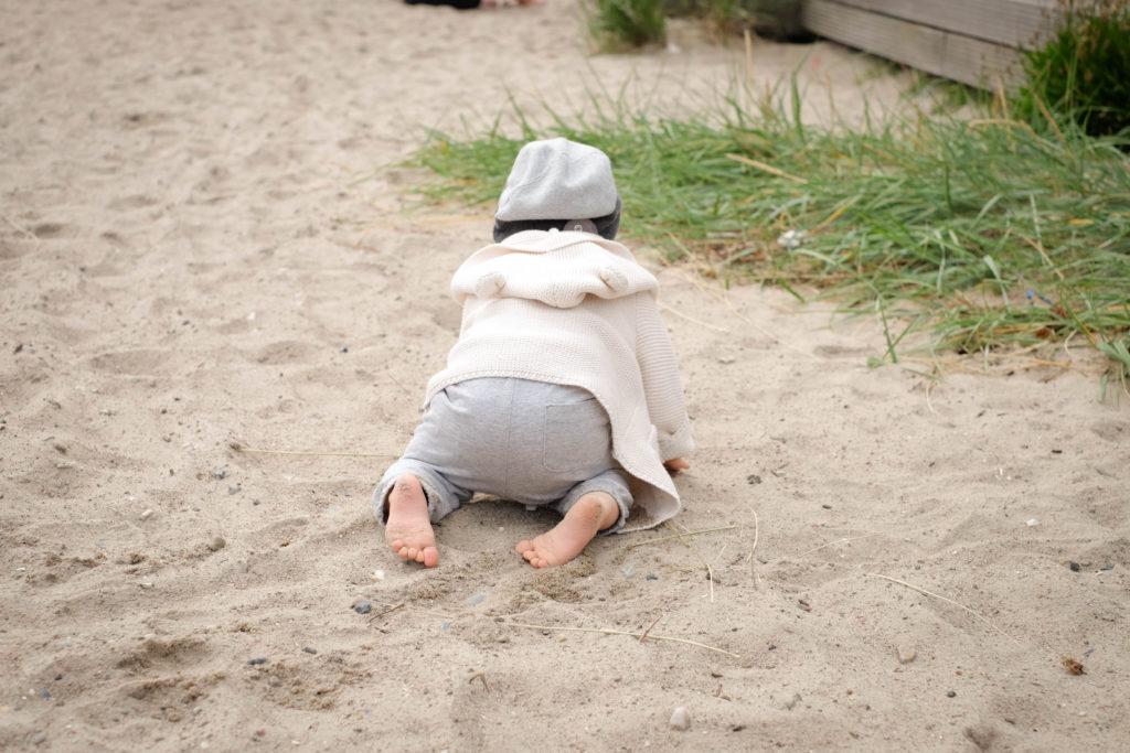 Unser Sohn Nikolas liebt es seine Umgebung zu entdecken und krabbelt aufgeregt im Sand umher.