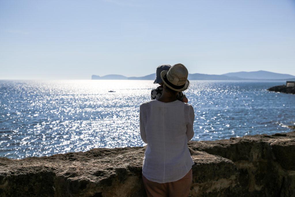 Julia mit Nikolas auf dem Arm schaut auf das Meer